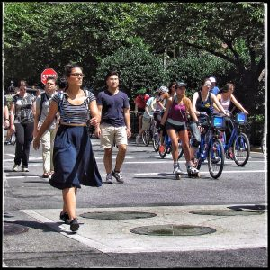 People on 5th Avenue walking, biking, and roller blading.